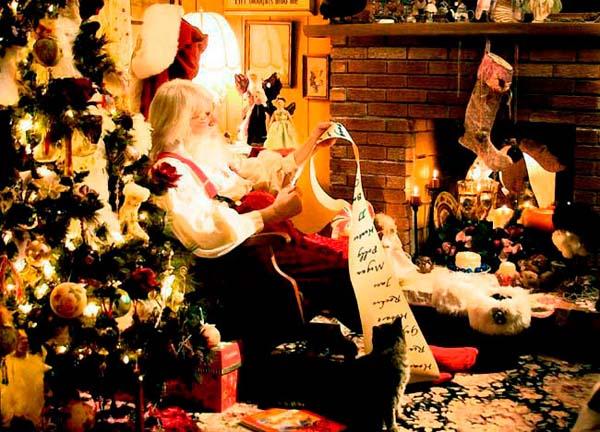 Santa sits by the fireplace checking his list, as Sheeba sits at his ...